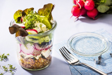 Dinkelsalat im Glas - Der bunte Schichtsalat ist in einem Gals angerichtet. Die Schichten Dinkel, Schafkäse, Radieschen, Salat und darauf Kresse sind gut zu erkennen. Neben dem Glas liegt der Deckel. Im Hintergrund liegt ein Bund Radieschen. Ebenso neben dem Glas liegt eine Gabel. (Foto: VrK/Alexander Stiegler - Nicht zur freien Verwendung)