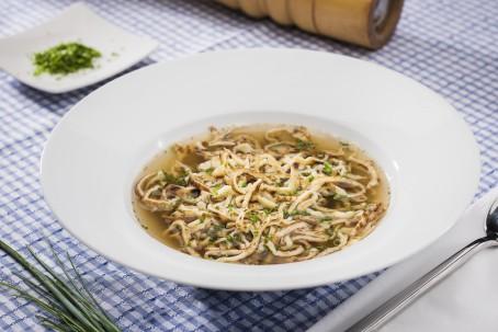 Frittatensuppe - In einem großen tiefen weißen Suppenteller ist eine Portion Rindssuppe mit Frittaten angerichtet. Darüber ist frischer Schnittlauch gestreut. (Foto: VrK/Alexander Stiegler - Nicht zur freien Verwendung)
