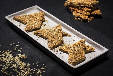 Hanf-Käse-Craker - Auf einer hellgrauen Platte liegen 6 Hanf-Käse-Craker - immer 2 Stück liegen schräg aufeinander. Die Kerne sind deutlich zu sehen. Im Hintergrund sind einige Craker zu einem Turm gestapelt. (Foto: VrK/Alexander Stiegler - Nicht zur freien Verwendung)