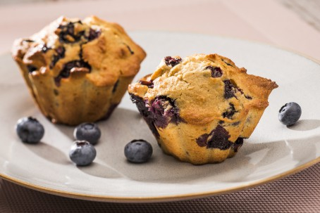 Heidelbeer-Kamut-Muffins - Auf einem weißen Teller sind 2 Muffins angerichtet. Die Heidelbeeren sind als lilafarbige Punkte im Muffin zu erkennen. Auf dem Teller liegen zur Deko einzelne Heidelbeeren verteilt. (Foto: VrK/Alexander Stiegler - Nicht zur freien Verwendung)