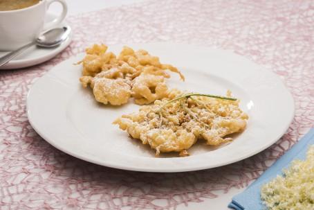 Hollerstrauben - Auf einem weißen runden Teller sind 2 Stück der goldgelben gebackenen Holunderstrauben angerichtet. Sie sind mit Staubzucker bestreut. (Foto: VrK/Alexander Stiegler - Nicht zur freien Verwendung)