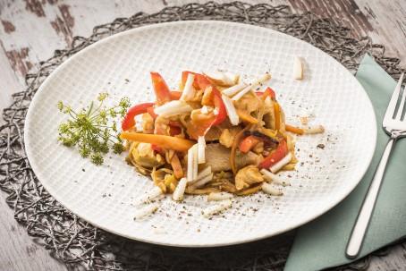Hühnerbrustfilets mit Birnenspalten - Auf einem runden weißen Teller mit Musterung sind die Geflügelstreifen mit Paprika, Birne und Mandelsplitter angerichtet. (Foto: VrK/Alexander Stiegler - Nicht zur freien Verwendung)