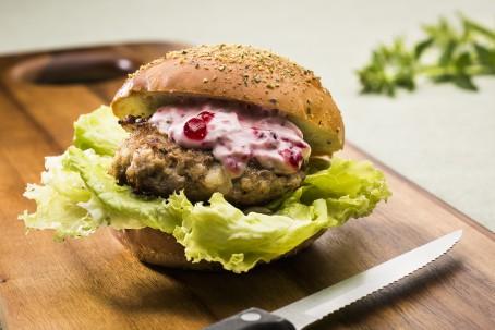 Rehburger - Auf einem braunen Holztisch liegt ein aufgeschnittenes Burgerweckerl mit einem Salatblatt auf dem ein saftig gebratener Burger, garniert mit einer weiß/roten Sauce (Foto: VrK/Alexander Stiegler - Nicht zur freien Verwendung)