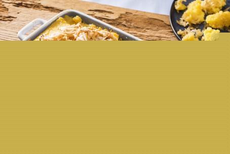 Polentatommerl mit Äpfeln - Auf einem Holzbrett steht eine blau/weiß karierte Auflaufform. Darin befindet sich goldgelb gebackener Polenta, garniert mit gehobelten Äpfeln und mit Zucker bestreut. Daneben liegt noch eine Gabel mit einer blauen Serviette (Foto: VrK/Alexander Stiegler - Nicht zur freien Verwendung)