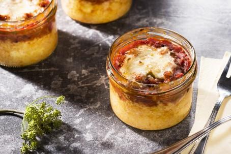 Maispizza - Auf grauem Untergrund steht ein Glas, in welchem die verschiedenen Zutaten geschichtet wurden; abgeschlossen mit geschmolzenem Käse. (Foto: VrK/Alexander Stiegler - Nicht zur freien Verwendung)