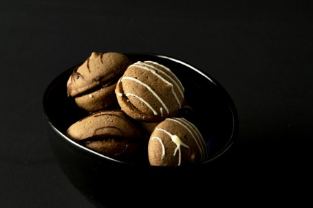 Schokoküsschen - Vor einem schwarzen Hintergrund steht ein schwarzes Schüsserl. DArin befinden sich einige der mit Schoklade zusammengeklebten Schokoküsschen. Verziert sind die Küsschen mit weißer und schwarzer Schokolade. (Foto: Tobias Schneider-Lenz - Nicht zur freien Verwendung)