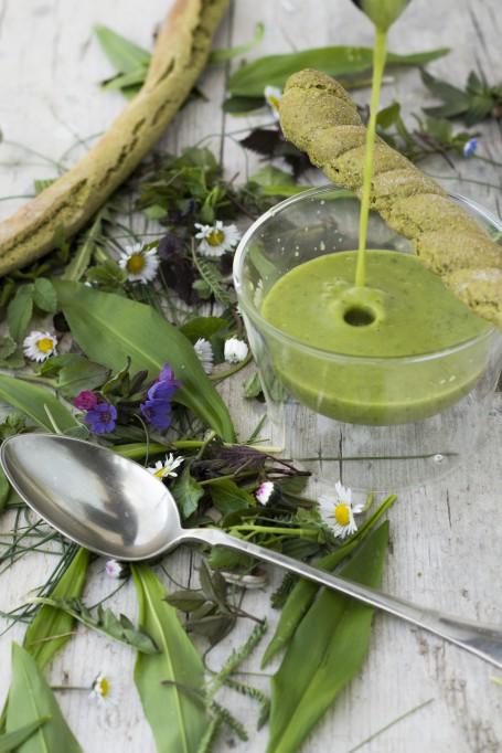 Wildkräutersupperl - In einem Glasschüsserl ist die grüne Cremesuppe angerichtet. Am Bild wird noch Suppe eingegossen. Schräg über dem Glasschüsserl liegt ein Grissinistangerl. Rund um das Gefäß sind Wildkräuter und Blüten verstreut. Ein silberner Esslöffel liegt im Vordergrund. (Foto: Tobias Schneider-Lenz - Nicht zur freien Verwendung)