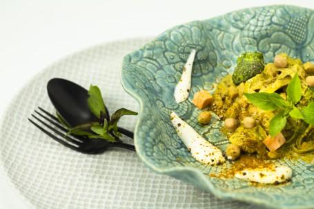 Gemüse-Rinder-Curry - Auf einem grün am Rand gerippten Teller mit Muster ist das gelbliche Curry angerichtet. Ein Kräuterblatt liegt dekorativ am Curry. Rund um die Portion sind Joghurttupfen platziert. (Foto: Tobias Schneider-Lenz - Nicht zur freien Verwendung)