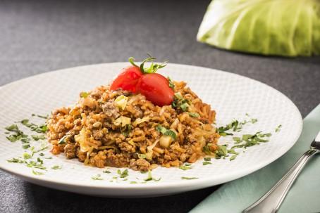 Reispfanne - Auf einem weißen Teller liegt eine Portion gelb/braun gefärbter Reis, garniert mit zwei roten Tomaten und Kräutern. Danebenliegt eine Gabel und eine Serviette (Foto: VrK/Alexander Stiegler - Nicht  zur freien Verwendung)