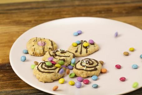 Schnelle Cookies - Auf einem leicht rosa Teller sind 4 Cookies zu sehen. Sie sind mit Schokolade, Smarties und Zuckerperlen verziehrt. Auf dem Teller sind auch noch einige Smarties um die Cookies verstreut. (Foto: Tobias Schneider-Lenz - Nicht zur freien Verwendung)