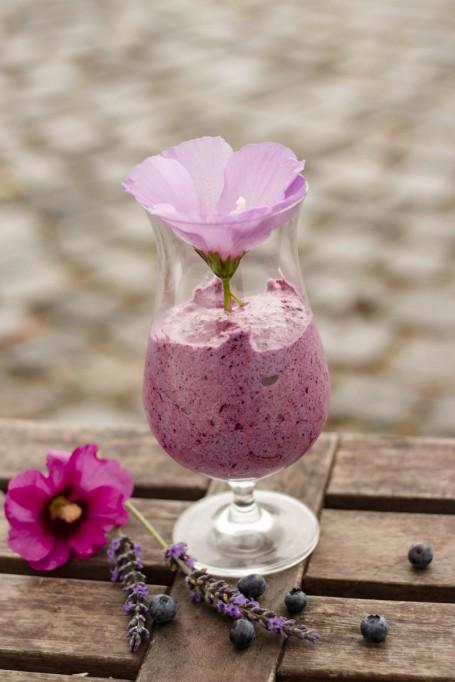 Luftiger Beeren-Hexenschaum - Auf einem Holzuntergrund steht in einem Cocktailglas serviert das lilafarben Dessert. Garniert ist das Dessert mit einer helllila Blüte. Vor dem Glas liegen einige Heidelbeeren, Lavendelblüten und eine dunkellila-farbige Blüte. (Foto: Tobias Schneider-Lenz - Nicht zur freien Verwendung)