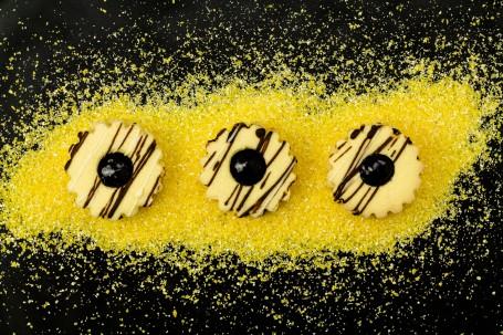 Kukuruz-Aronia-Spitzbuben - Auf schwarzem Hintergrund ist leuchtend gelber Maisgrieß gestreut. Darauf liegen 3 Stück der Spitzbuben. Das Marmelade in der Mitte des Lochs ist dunkel. Verziehrt sind die mit einem runden-gemusterten Ausstecher ausgestochenen Kekse mit weißen und dunklen Schokoladestrifen. (Foto: Tobias Schneider-Lenz - Nicht zur freien Verwendung)