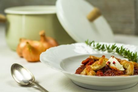 Hendl-Kürbis-Gulasch - In einem weißen Suppenteller ist das rötliche Hendl-Gulasch angerichtet. Die Hendl-Stücke sind hellbraun angeröstet und auf dem Gulasch platziert. Ein Tupen Sauerrahm ist als Dekoration am Gulasch angerichtet. Ein Kräuterzweig befindet sich am Tellerrand im Hintergrund. Hinter dem Teller sind verschwommen ein grünlicher Kochtopf und 3 Stück Zwiebel zu sehen. Links neben dem Suppenteller liegt ein Suppenlöffel bereit. (Foto: Tobias Schneider-Lenz - Nicht zur freien Verwendung)