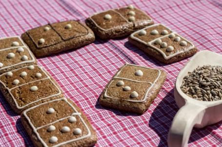 Waldstaudekorn-Weißmohn-Lebkuchen - Auf einem rot-weiß karriertem Tuch liegen sieben Stück des Lebkuchen. Die Kekse sind in Rechtecken ausgestochen und wie Dominosteine verziehrt und aneinander gereiht. Vorne rechts im Bild liegt eine Holz-Mehlschaufel mit Getreidekörnern darin. (Foto: Romana Schneider-Lenz - Nicht zur freien Verwendung)