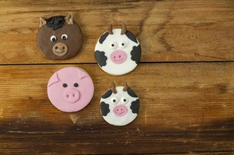 Mürbteig-Bauernhoftiere - Auf einer Holzoberfläche liegen 4 Stück der Bauernhofkekse. Sie sind rund und als Tiere verziehrt. Auf dem Bild sieht man einen braunen Esel, ein rosa Schwein und 2 schwarz-weiß-gefleckte Kühe. (Foto: Tobias Schneider-Lenz - Nicht zur freien Verwendung)