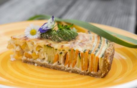 Einkorn-Gemüse-Quiche - Auf einem gelben Teller ist ein Stück der Gemüse Quiche angerichtet. Die abwechselnden Gemüseschichten sind deutlich zu erkennen und sehen sehr bunt aus. Der Überguss ist auf der Oberfläche leicht bräunlich. Auf dem Stück liegt ein Gänseblümchen und eine lila Blüte als Deko. Auch grüne Kräuterzweige sind dekorativ darauf platziert. (Foto: Moritz Lenz - Nicht zur freien Verwendung)