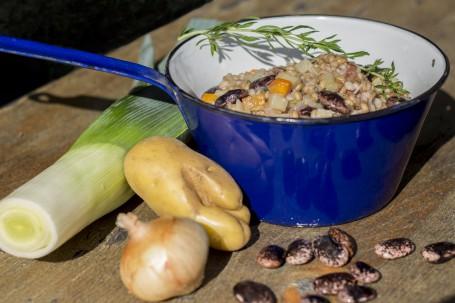 Ritschert - In einem kleinen blauen Topf mit einem langen Stiehl daran ist der Getreide-Gemüse-Bohnen-Eintopf angerichtet. Darüber liegt ein kleiner Rosmarienzweig. Links neben dem Topf liegt eine angeschnittene Lauchstange, einen Erdäpfel und eine Zwiebel. Vor dem Topf liegen einige gescheckte Bohnen verstreut. (Foto: Tobias Schneider-Lenz - Nicht zur freien Verwendung)