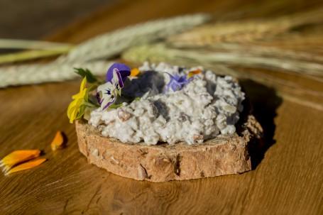 Rustikaler Grünkern-Speck-Aufstrich - Auf einer holzplatte liegt eine dicke Scheibe Brot auf dem sich eine Schicht des gräulichen Grünkern-Aufstriches befindet. Auf dem Aufstrich sind einige bunte Blüten gestreut. (Foto: Schneider-Lenz - Nicht zur freien Verwendung)