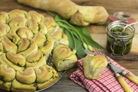 Grüne-Welle-Brot - Auf einer Holzplatte steht der Unterteil einer Tortenform. Auf der Form liegt das Grüne-Welle-Brot. Es besteht aus einzelnen