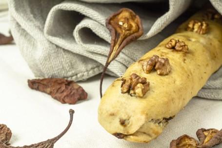 Früchtebrot im Mantel - Auf dem Bild ist ein längliches Früchtebrot in einem dünnen Teigmantel zu sehen. Auf dem Brot sind vier Nüsse zu sehen, die mitgebacken wurden. Verwinzelt liegen getrocknete Birnenhälften um das Brot herum. Das Brot ist zur hälfte in ein graues Tuch gewickelt, das im Hintergrund zu erkennen ist. (Foto: Tobias Schneider-Lenz - Nicht zur freien Verwendung)