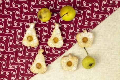Mostlandl Dinkel-Gewürzkekse - Auf einem rot-weiß gemustertem Tuch liegen fünf der Kekse. Drei haben eine Birnenform zwei sind als Apfelform ausgestochen worden. Sie sind mit einem hellgelben Marmelade zusammengesetzt und mit Staubzucker leicht besteut. Als Deko liegen drei kleine grüne Birnen zwischen den Keksen. (Foto: Tobias Schneider-Lenz - Nicht zur freien Verwendung)