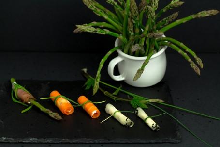 Gemüseröllchen mit Kräuterfrischkäse - Auf einer schwazen Schieferplatte auf schwarzem Hintergrund liegen 5 Gemüseröllchen. Zwei Karottenröllchen und zwei Käseröllchen mit Frischkäse gefüllt. Ganz links außen liegt ein Speckröllchen in der sich eine Spargelstange befindet. Die Käseröllchen sind an den Enden in Schwarzkümmel getaucht. Im Hintergrund steht ein weißer Topf mit grünen Spargelstangen darin. (Foto: Tobias Schneider-Lenz - Nicht zur freien Verwendung)