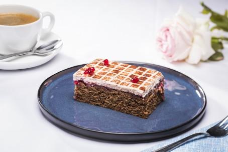 Käferbohnen-Preiselbeerschnitte - Auf einem runden blauen Teller ist ein rechteckiges Stück der Schnitte platziert. Auf dem dunklen Boden ist eine dünne Schicht der weißen Creme aufgetragen. Auf der Creme ist mit Kakaopulver ein Muster aus lauter kleinen Quadraten gestreut. Drei Preiselbeeren leigen auf dem Kuchenstück. Im Hintergrund liegt eine weiße leicht rosa schimmernde Rose und eine Tasse Kaffee mit Untertasse und Löffel sind dort platziert. (Foto: VrK/Alexander Stiegler - Nicht zur freien Verwendung)