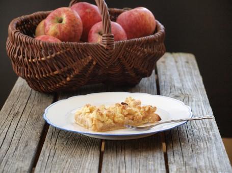 Apfel-Streuselkuchen - Auf einer Holzfläche steht ein weißer Teller mit blauem Rahmen, auf dem sich ein Stück des Apfel-Streuselkuchen befindet. Neben dem Kuchenstück liegt eine silberne Dessertgabel. Im Hintergrund steht ein großer brauner geflochtener Korb mit großen rotbackigen Äpfeln darin. (Foto: VrK/DI Carina Laschober- Luif - Nicht zur freien Verwendung)