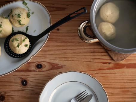Selchfleischknödel - Auf einem Holztisch steht ein silberner Suppentopf, der zur Hälfte mit Wasser gefüllt ist. Zwei selchfleischknödel schwimmen darin. In der linken Bildhälfte steht eine weiiße Porzellanplatte auf der einige fertige Knödel liegen und mit gehackter Petersilie bestreut sind. Im Vordergrund des Bildes steht ein weißer Teller mit goldener Verziwhrung auf dem sich Messer und Gabel befinden. (Foto: VrK/DI Carina Laschober- Luif - Nicht zur freien Verwendung)