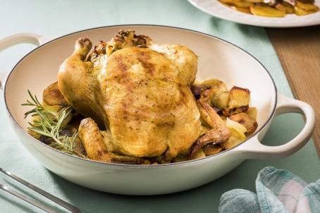 Aufgsetzte Henne - In einer weißen Schüssel mit Henkel liegt ein goldgelb gebratenes Hendl, auf einem Gemüsebett, garniert mit Kräutern (Foto: VrK/Alexander Stiegler - Nicht zur freien Verwendung)