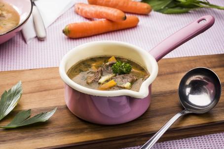 30-Minuten-Suppentopf - In einer hellrosa Stiekasserolle befinden sich Stück vom Rindfleisch, und Supengemüse; hainter liegen orangefarbene Karotten, daneben eine Schöpfkelle; (Foto: VrK/Alexander Stiegler - Nicht zur freien Verwendung)