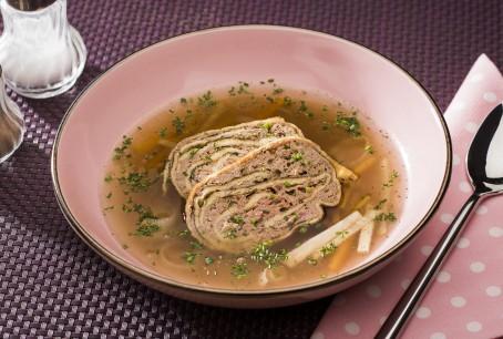 Leberroulade - In einem rosa Teller liegen zwei Stück der Leberroulade, ganiert mti Kräutern. In der Suppe befindet sich noch Suppengemüse (Foto: VrK/Alexander Stiegler - Nicht zur freien Verwendung)