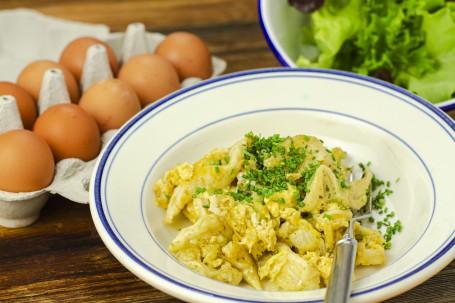 Eiernockel - Auf einem weißen Teller befinden sich die gelben Eiernockerl mit grünem Schnittlauch garniert. Daneben befindet sich eine Schüssel mit Salat und eine Eierbox mit Eiern. (Foto: Tobias Schneider-Lenz - Nicht zur freien Verwendung)