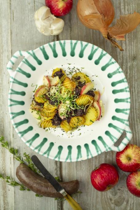 Blunzngröstl - Auf einem weiß/grünen Teller befindet sich das aus Erdäpfeln, Blunzn und Apfelscheiben bestehende Gröstl, ganiert mit grünen Kräutern. Daneben lieben Äpfel, Knoblauch, Zwiebel und ein Stück einer rohen Blunzn. (Foto: Tobias Schneider-Lenz - Nicht zur freien Verwendung)