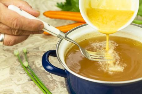 Eintropfsuppe - In einem blau/weißen Kochtopf befindet sich eine klare Flüssigkeit, in welche gerade die gelbe Eintropfmasse mit einer Gabel eingerührt wird. Daneben liegen orangefarbene Karotten. (Foto: Tobias Schneider-Lenz - Nicht zur freien Verwendung)