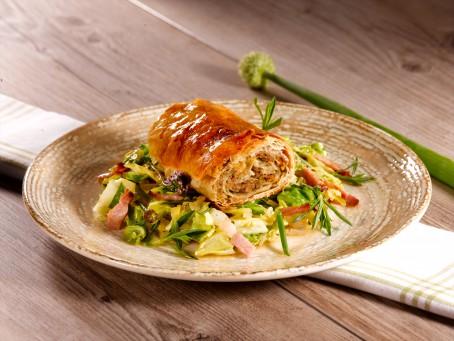 Knuspriger Leberstrudel & Leberstrudel in der Suppe - Auf einem braunen Teller liegt auf einem grünen Salatbett mit Speck ein Stück knusprig goldgelb gebackener Strudel. (Foto: VrK/Dall - Nicht zur freien Verwendung)