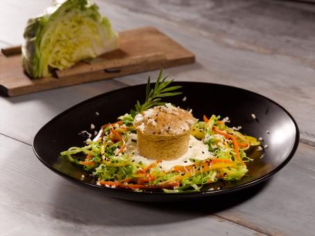 Soufflé von der Kalbsleber - Auf einem schwarzen Teller steht auf einem grün,orange, roten Gemüsebett ein braun gebackenes Soufflé ganiert mit Kräutern (Foto: VrK/Dall - Nicht zur freien Verwendung)