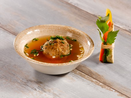 Leberknödel gekocht und gebacken - In einer braunen Schale liegt ein gekochter Leberknödel in einer goldbraunen Brühe, ganiert mit Schnittlauch. (Foto: VrK/Dall - Nicht zur freien Verwendung)