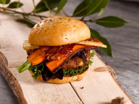 Leberburger - Auf einem Holzbrett liegt ein braun gebackenes Burgerbrötchen, gefüllt mit grünem Salat, braun gebratenem Burgerlaibchen, orangefarbenen Karotten, und knusprig gebratenem Speck. (Foto: VrK/Dall - Nicht zur freien Verwendung)