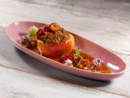 Bratapfel - Ein einer länglichen rosa Schale liegt ein rot/gelber Apfel, überbacken mit einer Leberfülle und garniert mit Preiselbeeren und Kräutern (Foto: VrK/Dall - Nicht zur freien Verwendung)