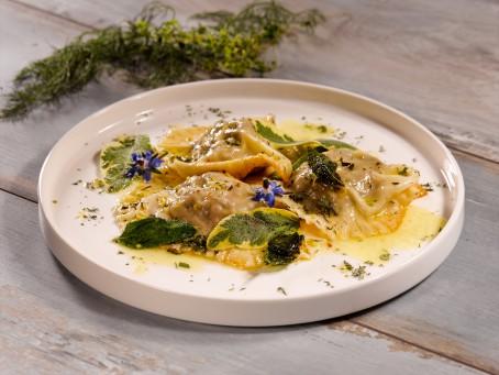 Leberravioli - In einer runden weißen Schale liegen 3Stk. gelbe Ravioli, garniert mit zerlassener Butter und Kräutern und Blüten. (Foto: VrK/Dall - Nicht zur freien Verwendung)
