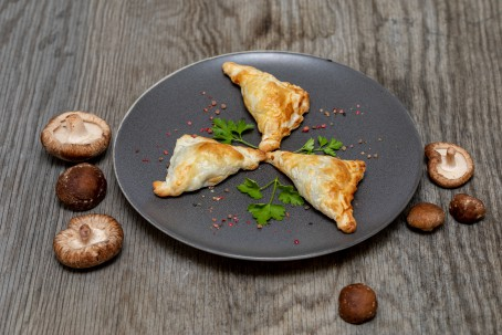 Blätterteigtaschen mit Pilzen - Auf einem dunkelgrauen Teller liegen 3 Stück Blätteteigtaschen. Dazwischen liegt jeweils ein Blatt Petersilie. Rund um den Teller sind Pilze gestreut. (Foto: VrK/Achim Mandler Photography - Nicht zur freien Verfügung)