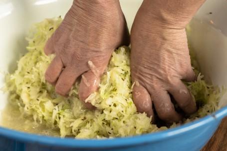 Sauerkraut 4 - In einem blauen großen Gefäß befindet sich gehobeltes Weißkraut. Zwei Hände kneten das Kraut kräftig durch. (Foto: Tobias Schneider-Lenz - Nicht zur freien Verfügung)