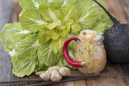 Würziges Kimchi - Es ist ein Glas gefüllt mit Kimchi - zerkleinerten und fermneitetem Chinakohl mit Karotten, Ingwer, Rettich und Gewürzen - zu sehen. An dem Glas ist seitlich dekorativ eine rote Chilischote am Glasrand eingehängt. Neben dem Glas ist eine schwarze Rettichknolle zu sehen. Links neben dem Glas liegt eine Ingwerknolle auf zwei Essstäbchen aus Holz. Im Hintergrund ist ein Chinakolh zu sehen. (Foto: Tobias Schneider-Lenz - Nicht zur freien Verwendung)
