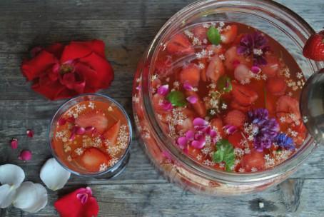 Kinderbowle - In einem großen runden Gefäß ist die Bowle angerichtet. Als Früchte wurden hier in erster Linie Erdbeeren verwendet. Die Erdbeerstückchen sind deutlich zu sehen. Es sind auch viele bunte Blüten in allen Farben und grüne Minzeblätter in der Bowle zu erkennen. Links neben dem Gefäß steht ein Glas in dem eine Portion Bowle angerichtet ist. Hinter dem Glas liegt eine große rote Blüte. (Foto: Romana Schneider-Lenz - Nicht zur freien Verwendung)
