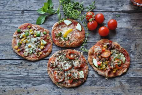 Lustiges Pizzagesicht - Auf dem Bild liegen vier verschieden belegte Pizzen. Auf einer Pizza ist ein Gesicht aus zwei Zucchinstücken als Augen, ein länglich geschnittener gelber Paprika als Nase und einige grüne Kräuter die als Mund in einem Halbkreis aufgelegt sind zu erkennen. Im Hintergrund liegen noch einige rote Tomaten und grüne Kräuter. (Foto: Romana Schneider-Lenz - Nicht zur freien Verwendung)