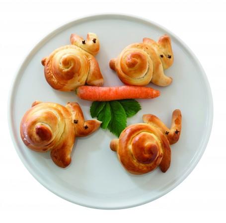 Osterhasen_Schmatzi - Auf einem runden Teller liegen vier Germteig Osterhasen. In der Mitte der Hasen liegt eine orange Karotte auf einem grünen Blatt. (Foto: Projekt Schmatzi – SeminarbäuerInnen / Stefanie Hueber - Nicht zur freien Verwendung)