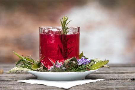Rauner küsst Whisky - Auf einem weißen Teller steht ein kleines Glas, darin befindet sich der rötliche Cocktail. Im Glas ist als Deko ein Rosmarienzweig platziert. Rund um das Glas liegen Kräuter und Blüten auf dem Teller. (Foto: Erwin Pils - Nicht zur freien Verwendung)