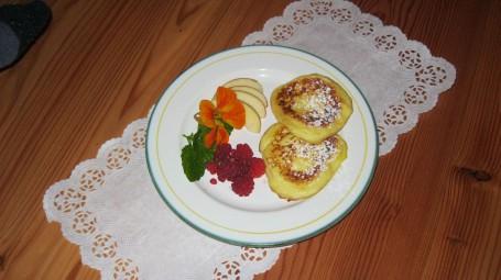 Flotte Topferl mit Frucht - Auf einem runden Teller befinden sich zwei goldbraun angebratene Topfenlaibchen mit Äpfeln und Himbeeren garniert. (Foto: Regina Putz - Nicht zur freien Verwendung)