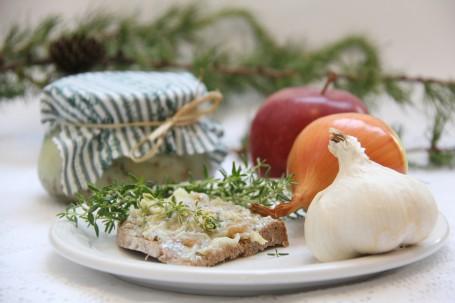 Würziges Kräuter-Grammelschmalz - Auf dem Bild sieht man das fertige Kräuter-Grammelschmalz. Davor ist ein Brot mit dem Aufstrich sowie zwei Ziebeln. (Foto: Elisabeth Heidegger - Nicht zur freien Verwendung)